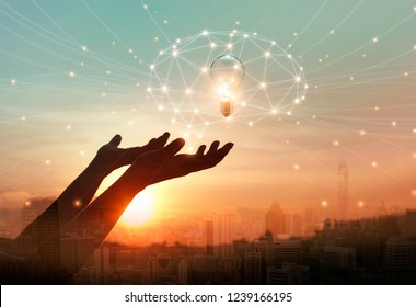 Abstract science. Hand holding brain digital network and light bulb inside on networking connection in city background. Idea and imagination. Creative and inspiration. Innovative technology