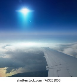 Abstract sci-fi background - extraterrestrial spaceship, UFO with bright blue spotlight flies near airplane in dark blue sky.