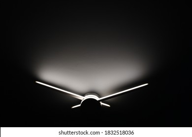 Abstract sconce lamp in shape of clock hands. Led lighting lamp closeup in darkness. Light and shadow abstraction