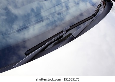 An abstract section of the front end of a silver vehicle and its front windscreen bonnet and wipers
