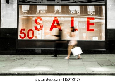Abstract shoppers walking past shop window with 50% sale