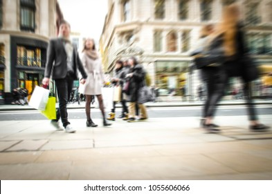 Abstract shopping street scene with anonymous shoppers walking and carrying shopping bags