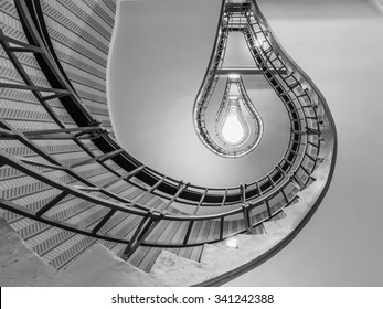 Abstract shot of a staircase leading towards a light bulb like opening