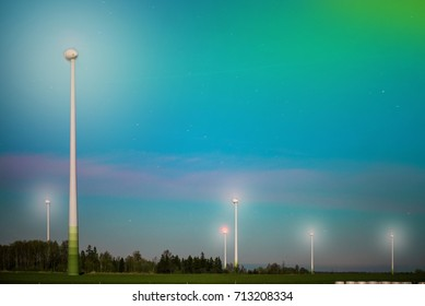 Abstract shot of wind turbines in the meadow on starry night sky background. Falling stars. Rural landscape, windmills producing electricity. Ecological life
