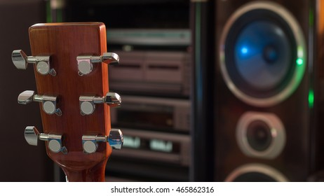 Abstract show details for head-stock classical guitar with speaker background.