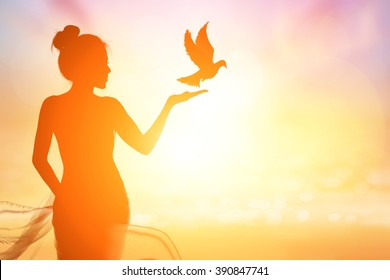 Abstract silhouette of bird flying out of lady hand on beautiful background.freedom concept ,International Working Women's Day
