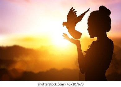 Abstract silhouette of bird flying out of lady hand on beautiful background.freedom concept and International Women's Day