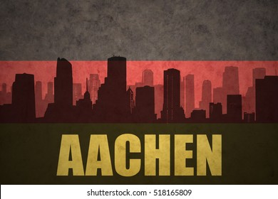 abstract silhouette of the city with text Aachen at the vintage german flag background