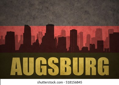 abstract silhouette of the city with text Augsburg at the vintage german flag background