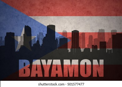 abstract silhouette of the city with text Bayamon at the vintage puerto rican flag background