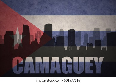 abstract silhouette of the city with text Camaguey at the vintage cuban flag background