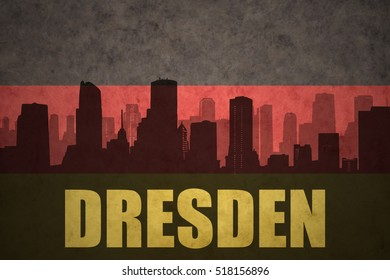 abstract silhouette of the city with text Dresden at the vintage german flag background