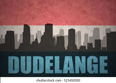 abstract silhouette of the city with text Dudelange at the vintage luxembourg flag background