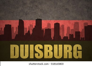 abstract silhouette of the city with text Duisburg at the vintage german flag background