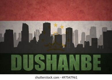 abstract silhouette of the city with text Dushanbe at the vintage tajikistan flag background