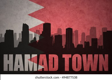 abstract silhouette of the city with text Hamad Town at the vintage bahrain flag background