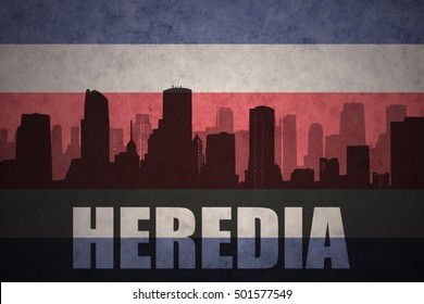 abstract silhouette of the city with text Heredia at the vintage costa rican flag background