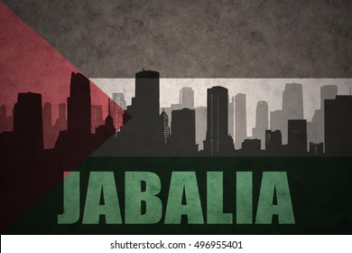 abstract silhouette of the city with text Jabalia at the vintage palestinian flag background