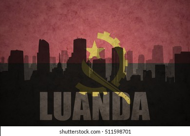 abstract silhouette of the city with text Luanda at the vintage angolan flag background