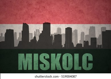 abstract silhouette of the city with text Miskolc at the vintage hungarian flag background