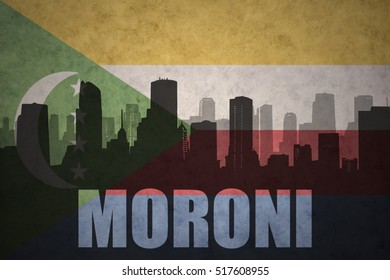 abstract silhouette of the city with text moroni at the vintage comoros flag background