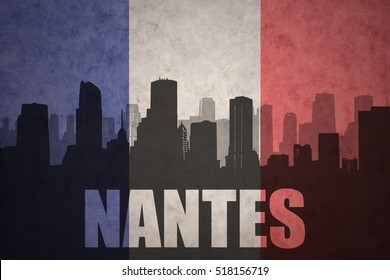 abstract silhouette of the city with text Nantes at the vintage french flag background