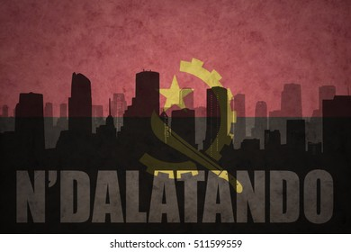 abstract silhouette of the city with text N'dalatando at the vintage angolan flag background