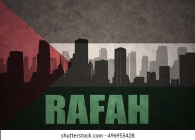 abstract silhouette of the city with text Rafah at the vintage palestinian flag background