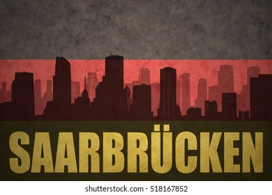 abstract silhouette of the city with text Saarbrucken  at the vintage german flag background