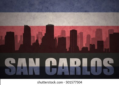 abstract silhouette of the city with text San Carlos at the vintage costa rican flag background