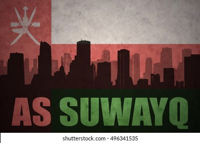 abstract silhouette of the city with text As Suwayq at the vintage oman flag background