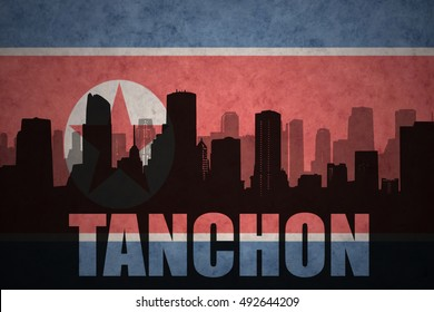 abstract silhouette of the city with text Tanchon at the vintage north korea flag background