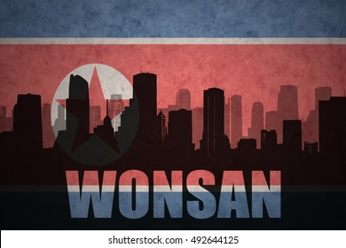 abstract silhouette of the city with text Wonsan at the vintage north korea flag background