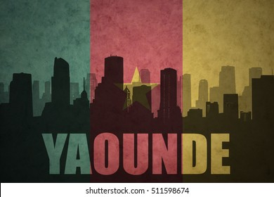 abstract silhouette of the city with text Yaounde at the vintage cameroon flag background