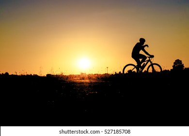 Abstract silhouette of  men on mountain-bike with beautiful sky at sunset .