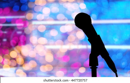Abstract with silhouette of microphone on stage and blurry colorful bokeh of Concert lighting, copy space