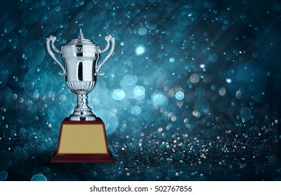 abstract silver trophies with blue bokeh lighting. copy space ready for your trophy design.