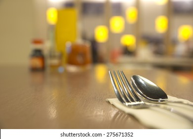 Abstract silverware on top of table with blurry restaurant background