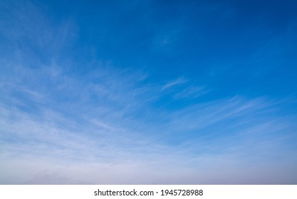 An abstract sky background of blue with wispy white clouds towards the bottom
