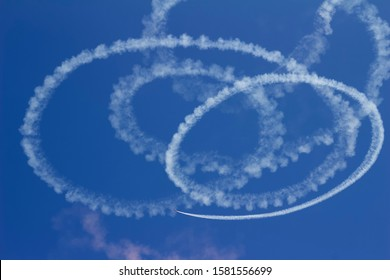 Abstract skywriting design with spiraling circles of vapor against a solid blue sky