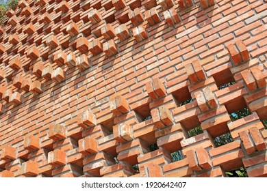 Abstract slanting view of an exterior garden wall designed with square holes in the brickwork and bricks that jut out from the wall