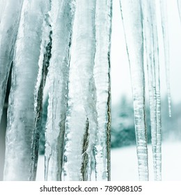 Abstract snowy winter scene background of heavy melting icicles closeup of crystal clear frozen water hanging down from cozy cottage roof at Christmas. White snow and ice season landscape. Window view