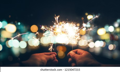 Abstract sparklers with city night light for christmas and new year eve celebrate holiday background, vintage color tone process style