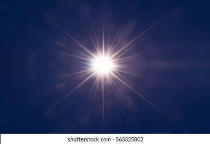 Abstract sparkling light rays and lighting flare bokeh against on dark blue sky background