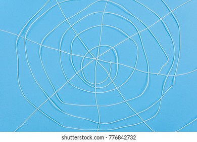 Abstract spiderweb, white threads on blue background.
