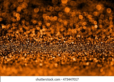 Abstract spooky dark orange and black glitter sparkle fright night background for Halloween trick or treat party invitation or flyer