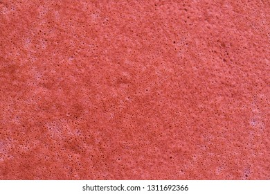 abstract spotty and porous organic texture closeup for a background or for wallpaper of red fiesta color