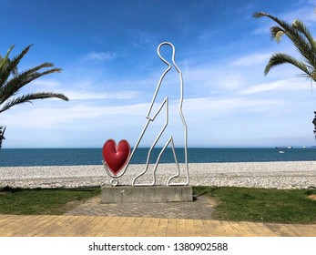 Abstract statues, small architectural forms of a man carrying a heart on a trolley on Batumi Seaside Boulevard or Batumi Beach. Georgia, Batumi, April 17, 2019.