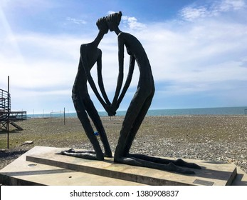 Abstract statues, small architectural forms of people in love in the form of a kneeling knee on the Batumi Primorsky Boulevard or Batumi Beach. Georgia, Batumi, April 17, 2019.