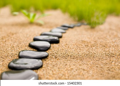 Abstract stone path on sand on a background of a grass